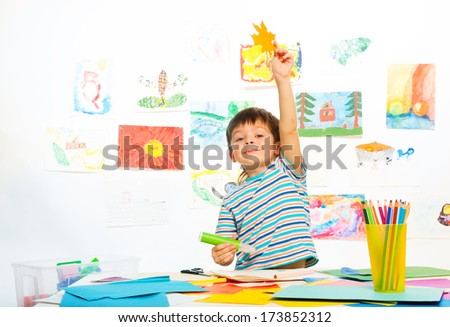 Boy in early development class cut paper and glue holding paper maple leaf - stock photo