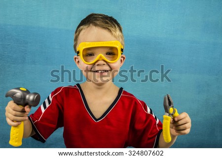 Boy in goggles and construction tools - stock photo