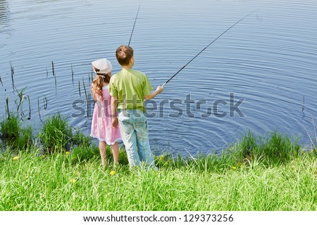 Boy in green t-shirt and his sister in pink dress fish in pond - stock photo