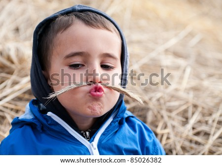 Boy in haystack with toy mustaches made of spikelets - stock photo