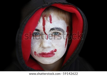 Boy in hood with painted face on halloween. - stock photo