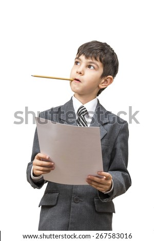 boy in jacket holding a pencil in his mouth and thinks holding a cookie sheet of paper - stock photo
