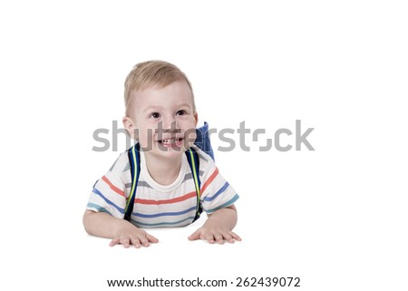 Boy in jeans with suspenders lying on his stomach and laughing isolated on white background - stock photo