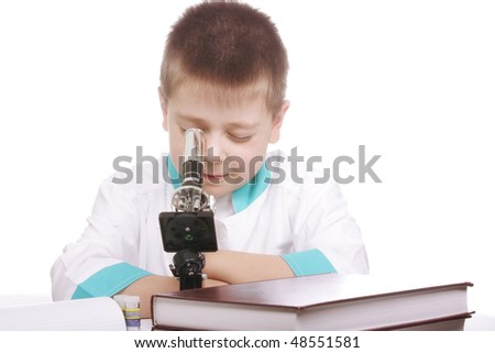 Boy in lab smock looking into microscope against white background