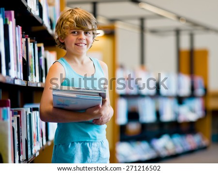 Boy in library choosing books - stock photo