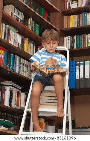 Boy in library reading book - stock photo