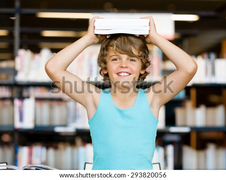 Boy in library with books - stock photo