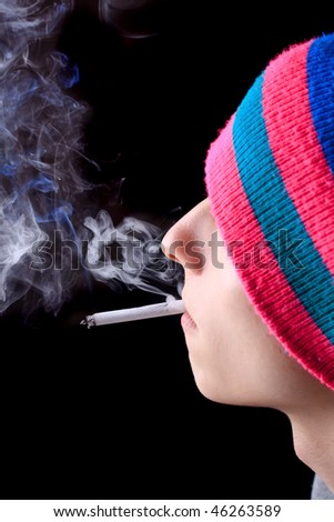 Boy in multicolored hat smokes - stock photo