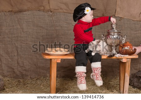 boy in national costume sits in the cart, there are pancakes and plays with a cat sitting on the bench - stock photo