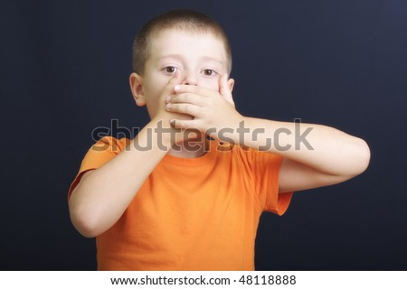 Boy in orange shutting mouth with hands against dark background - stock photo