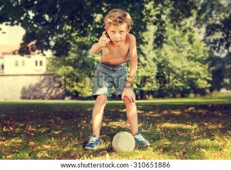 Boy in park ready to kick ball  - stock photo