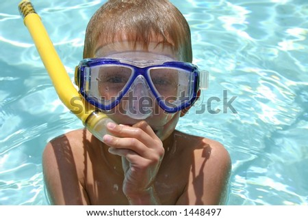 boy in pool with snorkel gear - stock photo
