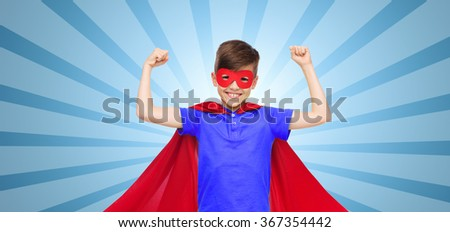 boy in red super hero cape and mask showing fists