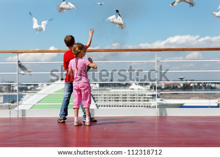 Boy in red t-shirt and his younger sister feed seaguls on deck of ship. - stock photo