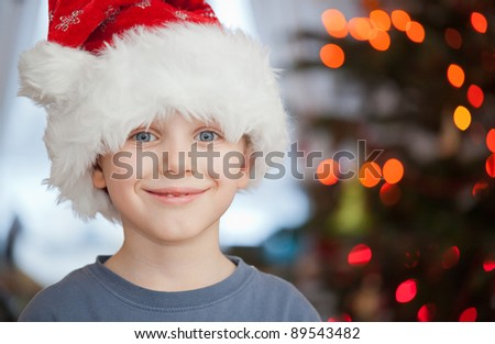 Boy in santa claus hat having fun in christmas day - stock photo