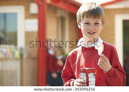 Boy In School Uniform Eating Potato Chip In Playground - stock photo