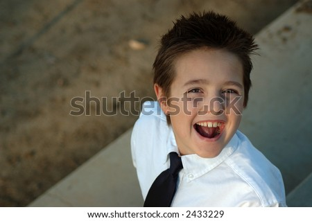 Boy in school uniform looking up; copy space included - stock photo