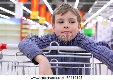 boy in shop with  cart - stock photo