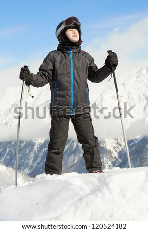 Boy in ski suit stands leaning on ski poles and looking upward, blue sky and mountains on background - stock photo