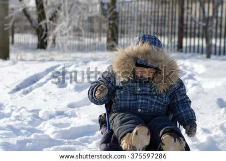 Boy in sledge on snow blinked in the wind against the background of the fence
