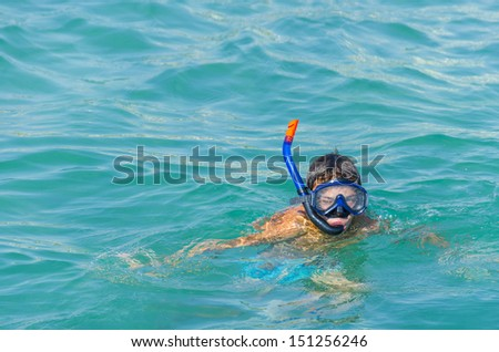 Boy in snorkeling mask with snorkel at sea, ocean green water - stock photo