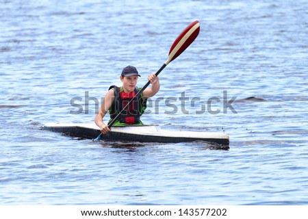 Boy in sport kayak paddles on the water - stock photo