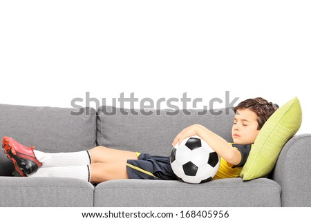 Boy in sportswear with a football sleeping on a modern sofa isolated on white background - stock photo