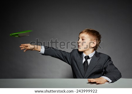 Boy in  suit launching green paper plane