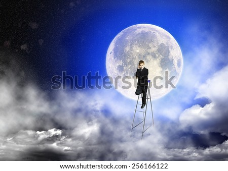 Boy in suit stands on a step-ladder against the background of a full moon and a starry sky - stock photo