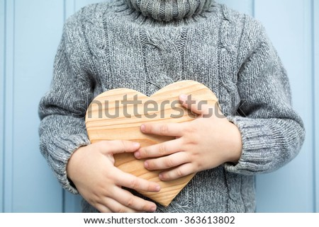 boy in sweater holding a wooden heart on the background of wooden wall - stock photo