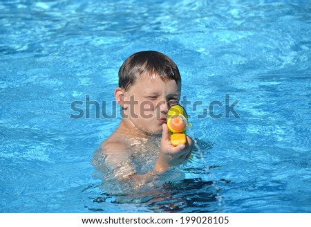boy in swimming pool playing with water gun