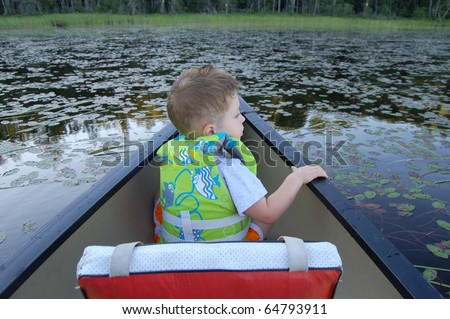 Boy in the bow of a canoe searches the lily pads for frogs/Look for Adventure/Take time to look around and find new treasures - stock photo