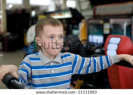 Boy in the children's amusement arcade. Playing a video game.