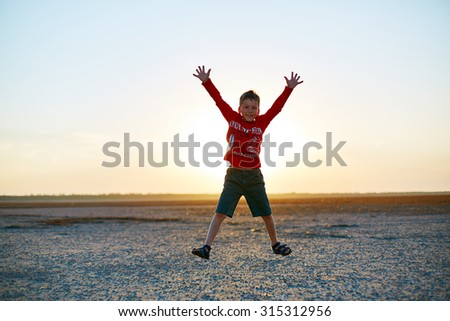 boy in the desert at the  sunset - stock photo