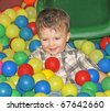 boy in the dry pool with colored balls - stock photo