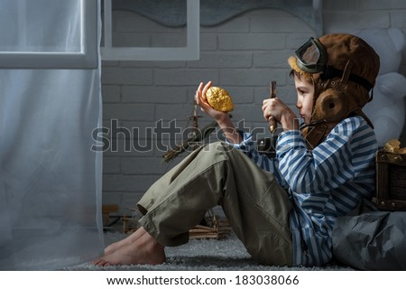 Boy in the image airplane pilot studies found a treasure in my room in the moonlight  - stock photo