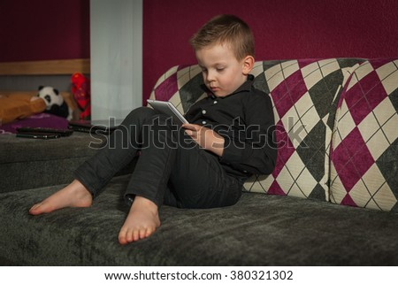 boy in the living room on the couch playing on tablet