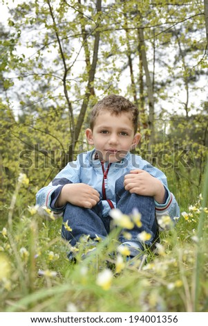 Boy   in the spring woods sitting  near the flowers. - stock photo