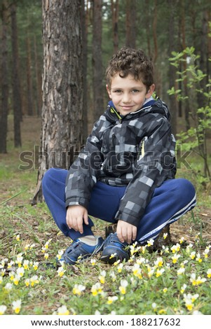 Boy in the spring woods sitting on a stump near the flowers.