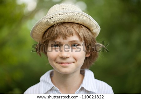 Boy in the striped shirt woven hat with a smile on your face - stock photo