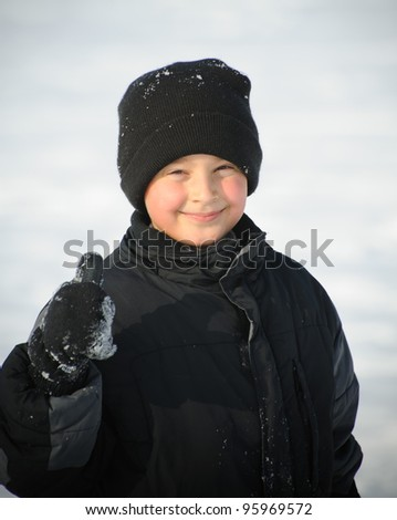 Boy in the winter showing thumb up - stock photo