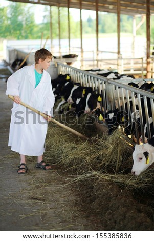Boy in white coat loads hay by big pitchfork for calves at large farm.  - stock photo