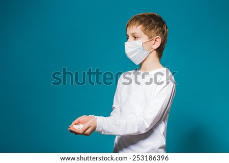 Boy in white protection mask holding pills in hand - stock photo
