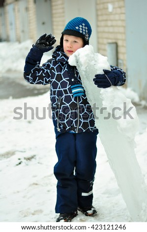 boy in winter with snow in the hands of light day - stock photo