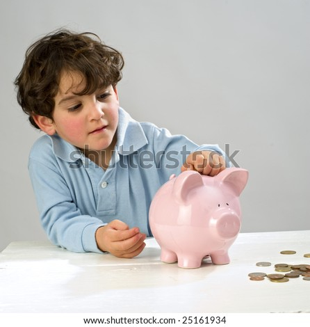 boy inserting a coin in a piggy bank - stock photo