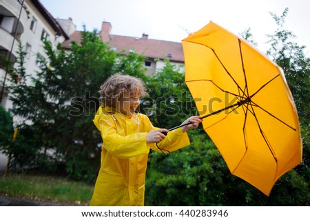 Boy is closed by a big yellow umbrella from a rain and wind. He hardly holds an umbrella. Chappie has closed eyes. - stock photo