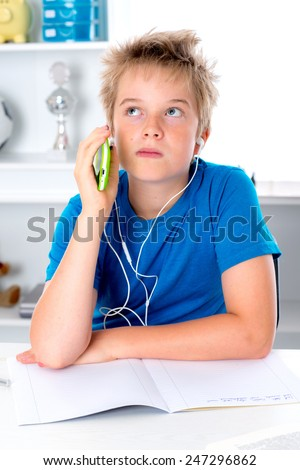 boy is doing homework and listening music - stock photo