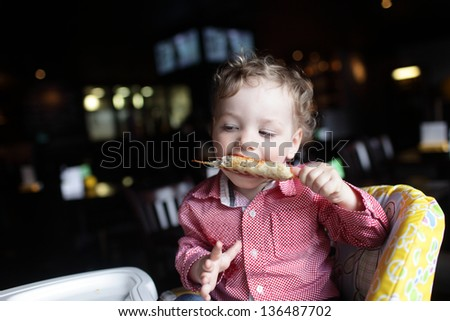 Boy is eating kebab in a high chair at a restaurant - stock photo