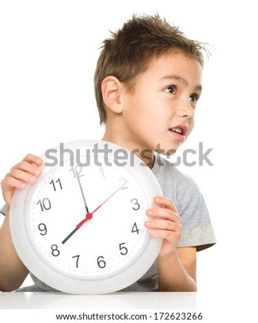 Boy is holding big clock showing eight a.m., isolated over white