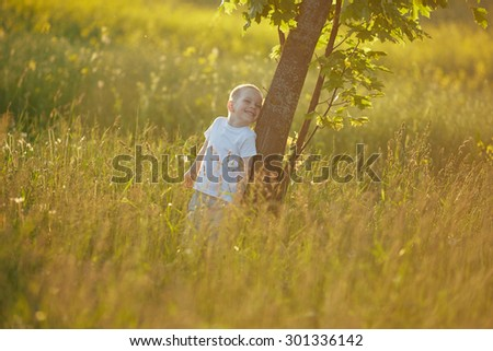boy is leaning against a tree